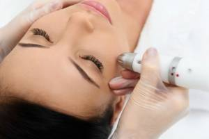 Close up of beautician hand moving laser over female facial skin. Young woman is lying and enjoying massage