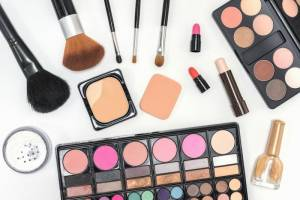 Collection of makeup cosmetics palette, lipstick and brushes on white background flat lay style