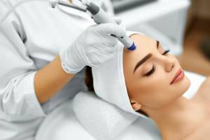 Face Skin Care. Close-up Of Woman Getting Facial Hydro Microdermabrasion Peeling Treatment At Cosmetic Beauty Spa Clinic.